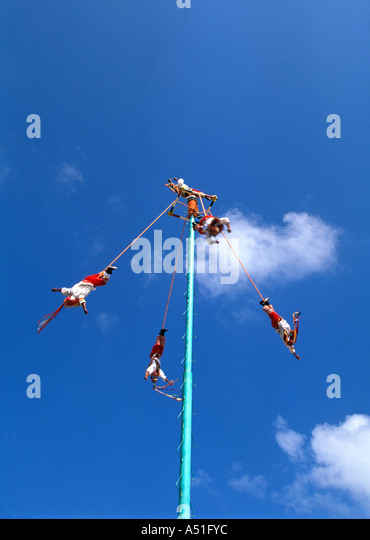 Tulum Mexico Mayan pole dancers voladores five costumed men ceremonial ritual whirl down high pole - Stock Image