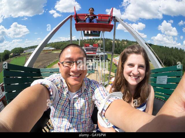 An interracial couple take a selfie on a Ferris wheel at Fort Edmonton Park in Edmonton, Alberta, Canada. - Stock Image