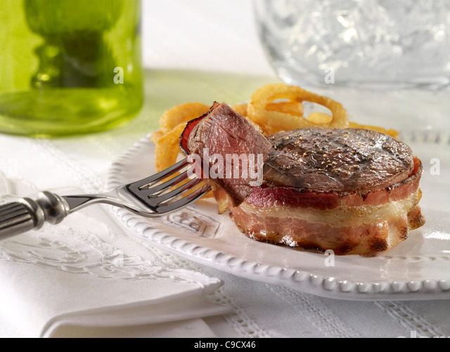 Beef Tenderloin wrapped in bacon and served with onion rings - Stock Image