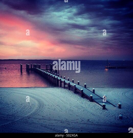Dock at sunset with walkway buried in the sand. - Stock Image