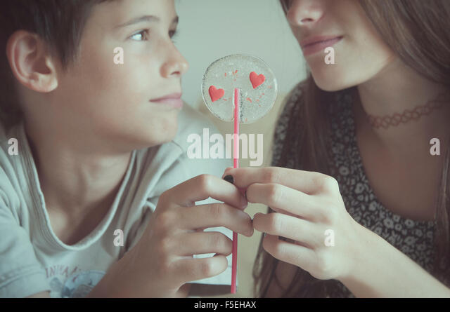 Boy and girl holding valentine day's lollipop - Stock Image