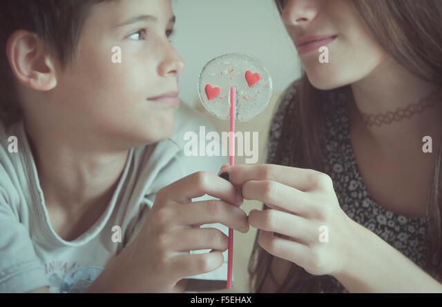 Boy and girl holding valentine day's lollipop - Stock-Bilder