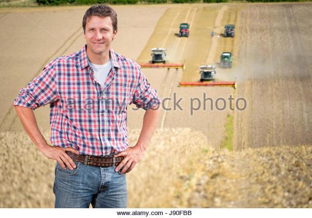 Portrait Of Farmer Standing In Wheat Field At Harvest - Stock-Bilder