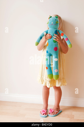 Girl holding stuffed animal in front of her - Stock Image