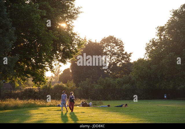 Young people walking at dusk in a London park - Stock Image