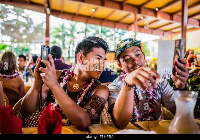 Two young men reading menu in Polynesian Cultural Centre, Hawaii, USA - Stock Image