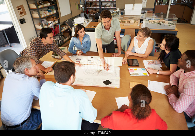 Group Of Architects Sitting Around Table Having Meeting - Stock Image