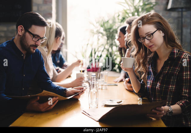 Group of happy business people eating together in restaurant - Stock Image