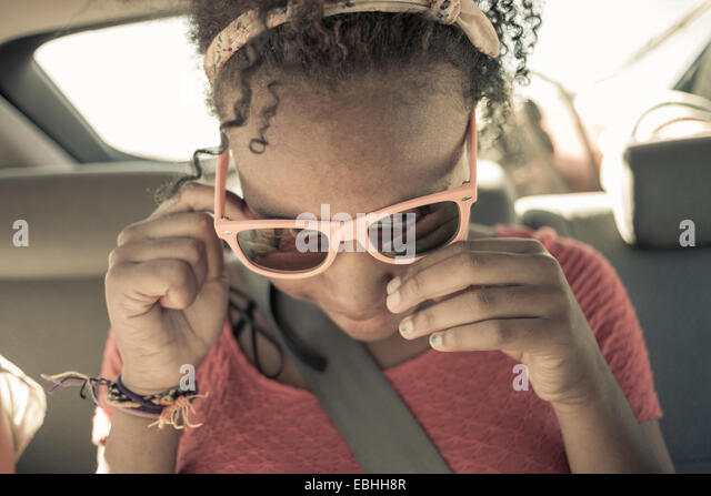 Close up of girl peering though sunglasses on car back seat - Stock Image