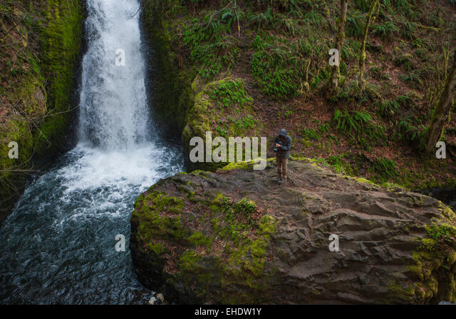 male photographer standing on a large rock right beside a massive waterfall in bridal falls oregon reviewing his - Stock Image