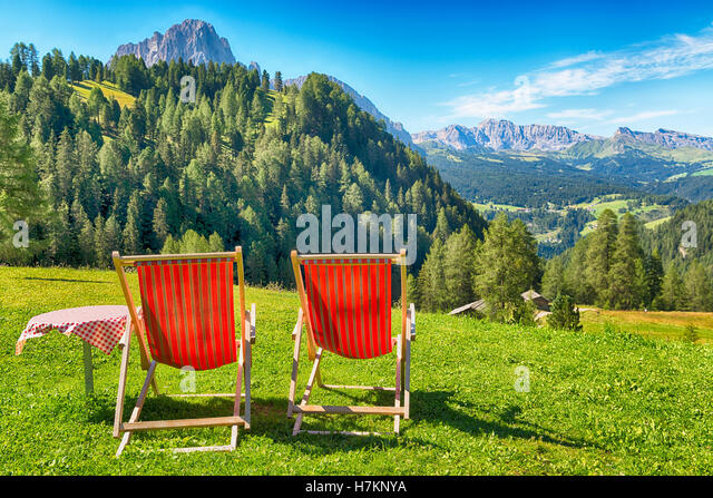 deck chairs and table on the lawn overlooking the mountains and the valley in summer - Stock Image