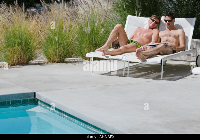 Gay couple relaxing by swimming pool - Stock Image