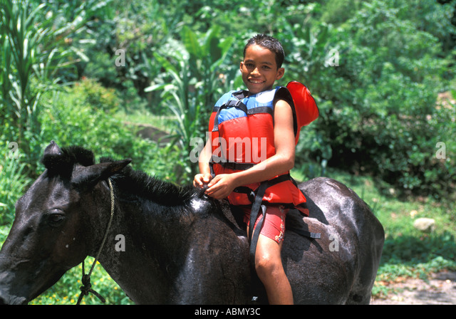 Honduras boy wearing life jacket riding horse - Stock Image