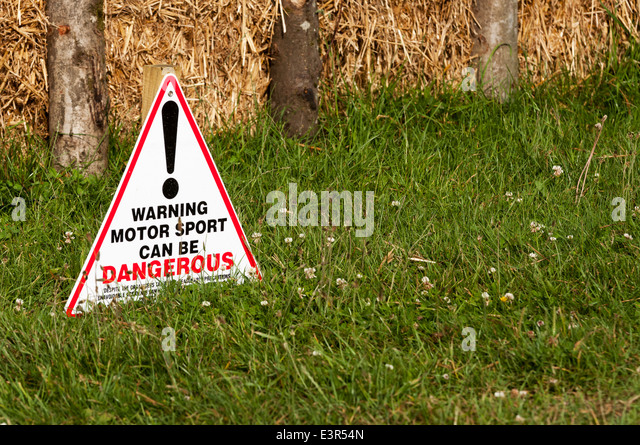 Sign at motor sport event explaining that motor sport can be dangerous - Stock Image