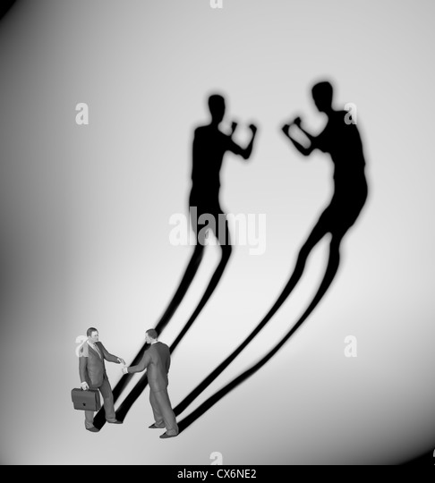 Two businessman casting a shadow shaped like two fighters - Stock-Bilder
