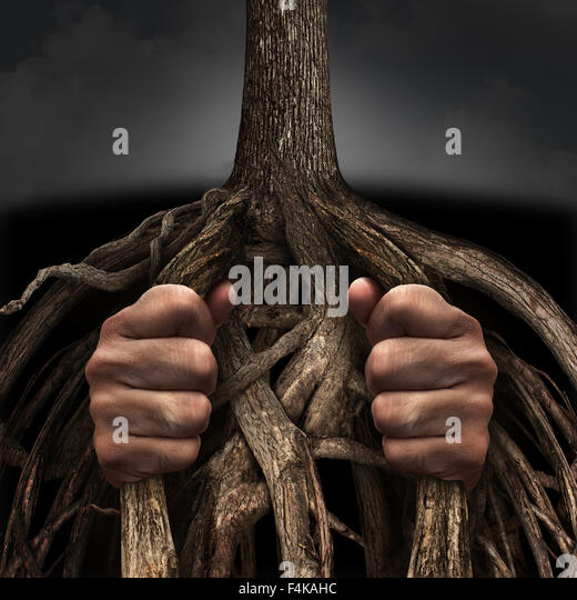 Trapped concept and mental prison symbol as a person caged and imprisoned by the slow growing roots of a tree as - Stock Image