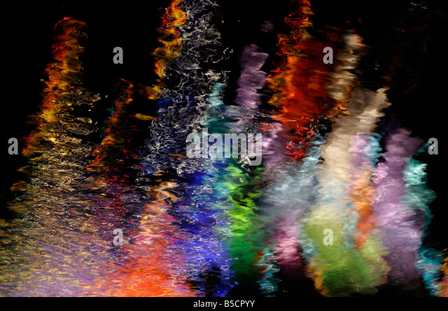 Abstract reflections of colored lights at night in moving water ripples - Stock-Bilder