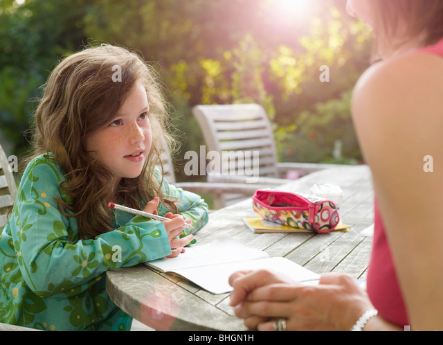 Young girl and mother chatting in garden - Stock-Bilder