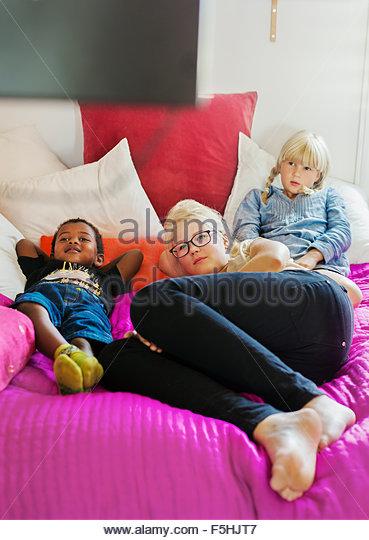 Denmark, Siblings (4-5, 10-11, 14-15) watching TV at home - Stock-Bilder