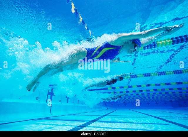 Young female professional participants racing in pool - Stock Image
