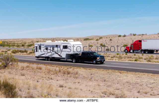 Pickup towing fifth wheel travel trailer on I-10 in southeastern Arizona one person visible - Stock-Bilder