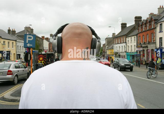 Rückansicht des Mannes mit rasierten Kopf und Tattoo tragen von Kopfhörern Stockbild