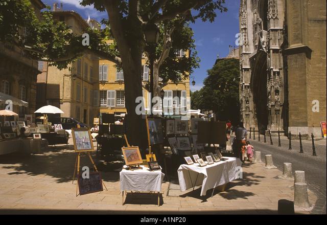 Gemälde zum Verkauf auf Leinen gedeckte Tische auf einem sonnigen Platz in Aix in Provence - A Street Szene Stockbild