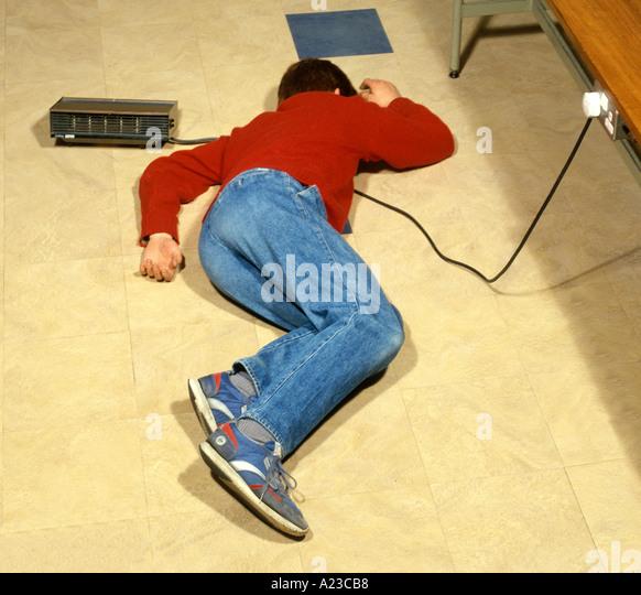 ein Teenager, die Lügen über elektrische Kabel verbunden, eine elektrische Heizung Strom kann gefährlich Stockbild