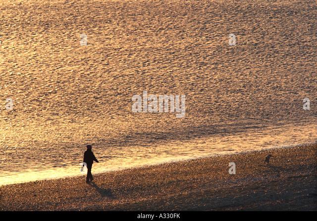 Person zu Fuß ihren Hund entlang der Uferlinie auf einem Kiesstrand Stockbild