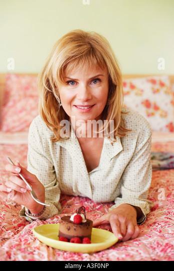 Porträt einer reifen Frau auf dem Bett liegend und Kuchen essen - Stock-Bilder