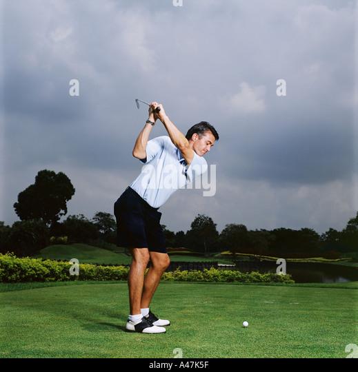 Mann schwingenden Golfclub Stockbild