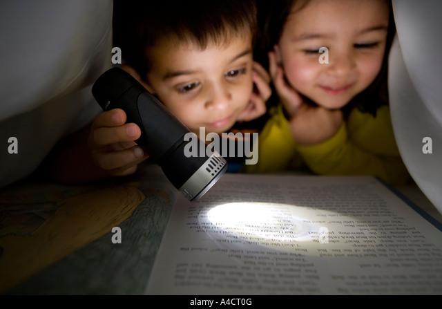 Jungen und Mädchen lesen ein Buch Taschenlampe unter der Bettwäsche Stockbild