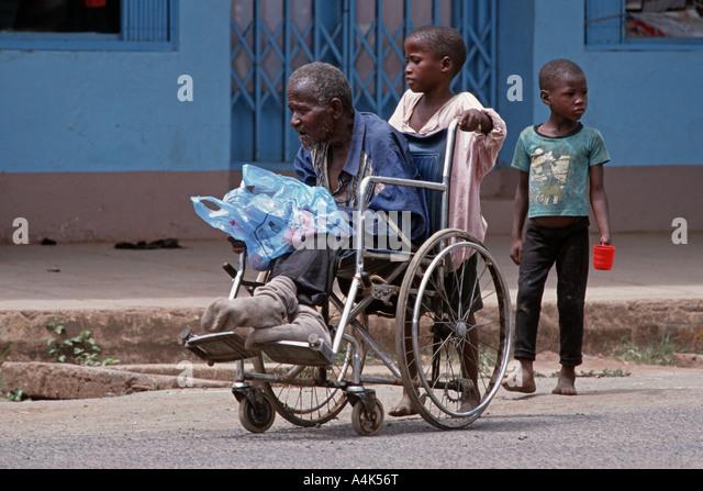 Kinder schieben eines Rollstuhls mit einem behinderten Verwandten zum Betteln auf den Straßen von Moshi, Tansania Stockbild