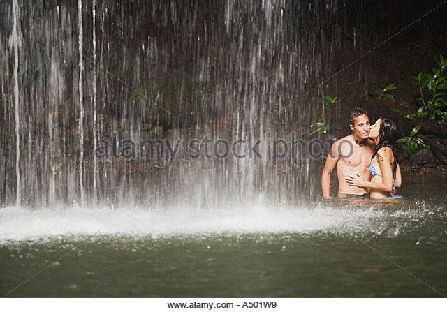 Junges Paar unter Wasserfall Stockbild