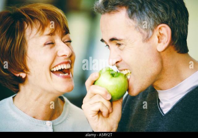 Ältere Menschen essen Apfel, senior Frau lachend, Nahaufnahme Stockbild