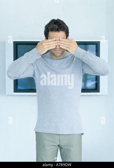 Mann übergibt stand vor Breitbild-TV, Augen Stockbild