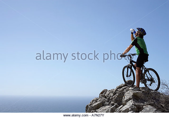Männliche Mountainbiker sitzt auf Fahrrad am Rand des Felsens Blick auf Horizont über Meer Rückansicht Stockbild