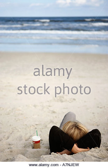 Frau Entspannung am Sandstrand neben Einweg Tasse liegen auf hinteren Hände hinter Kopf Blick auf Horizont Stockbild