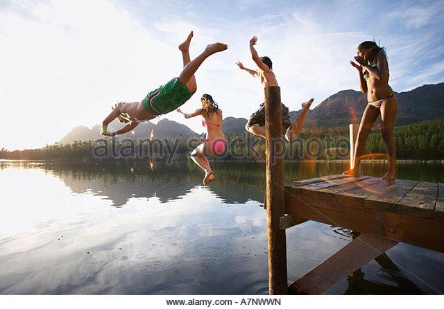 Vier junge Erwachsene Tauchen von der Anlegestelle in See bei Sonnenuntergang Seite Ansicht Lens flare Stockbild