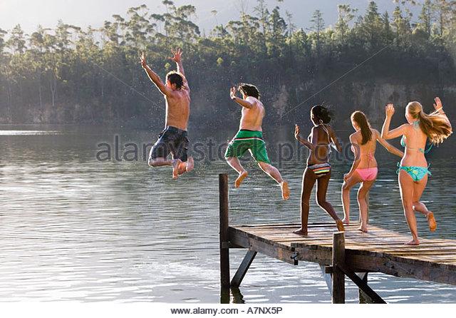 Fünf junge Erwachsene in Badebekleidung nebeneinander von der Anlegestelle in See hinten springen anzeigen Stockbild