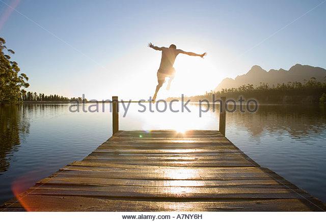 Mann springt von der Anlegestelle in See bei Sonnenuntergang Rückansicht Lens Flare Hintergrundbeleuchtung Stockbild