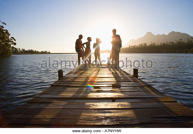 Familie in Bademode stehen am Rand See Mole bei Sonnenuntergang Lens flare Stockbild