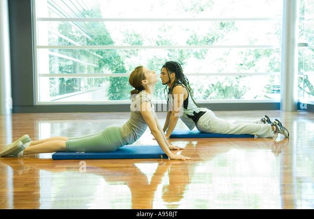 Zwei junge Erwachsene tun Cobra posieren in Yoga-studio Stockbild