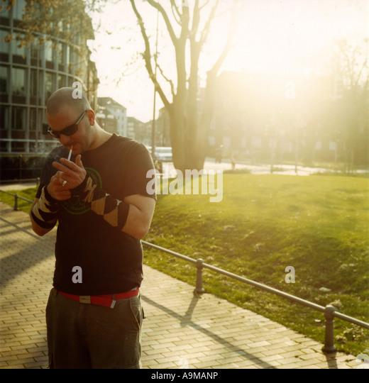 junger Mann Rauchen außerhalb - Stock-Bilder
