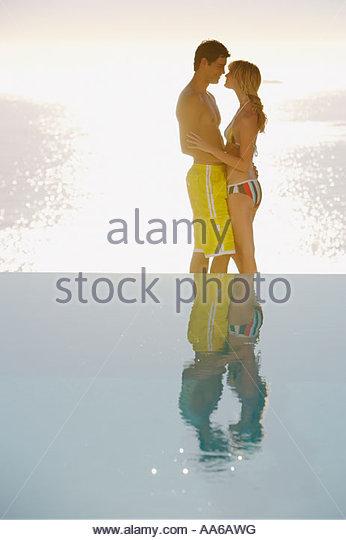 Profil von Mann und Frau in Badeanzügen im Freien mit Wasser umarmen Stockbild