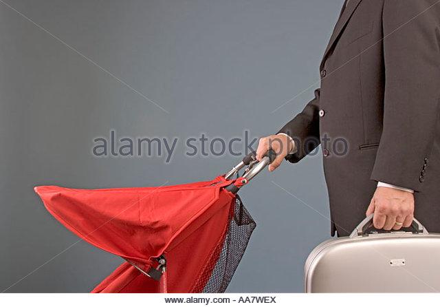 Geschäftsmann mit Aktenkoffer und Kinderwagen schieben Stockbild