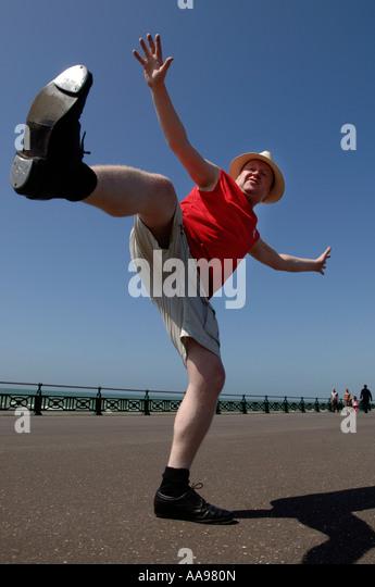 Ein übergewichtiger Mann mittleren Alters dabei ungeschickt hohen munter Tanz-Routine auf Brighton seafront Stockbild