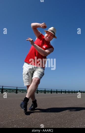 Ein übergewichtiger Mann mittleren Alters hart konzentrieren und dabei ungeschickt Tanz-Routine auf Brighton Stockbild