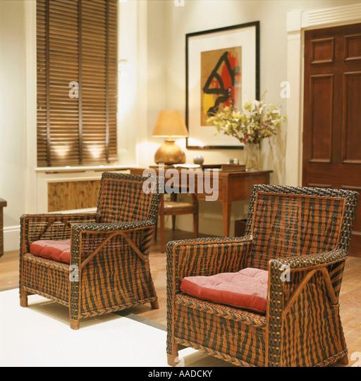 Passende gemusterte Wicker Sessel mit roten Kissen Stockbild