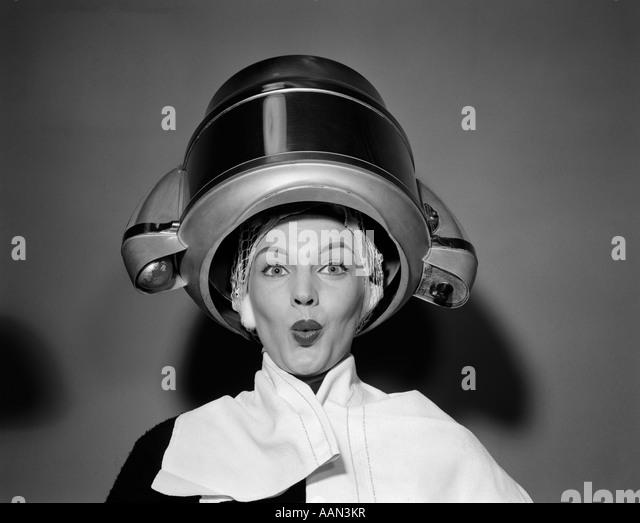 1950ER JAHREN FRAU UNTER HAARTROCKNER MIT HANDTUCH AUF SCHULTERN UND HAARE NET BLICK IN DIE KAMERA Stockbild